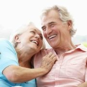 Older couple sitting and laughing, enjoying life without the worry of an enlarged prostate (BPH).
