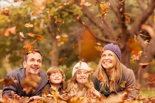 Family throwing leaves in the air during the fall season.