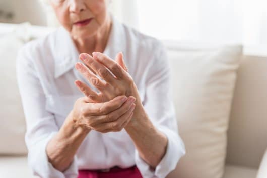 Older woman grasping hand that is suffering from arthritis.