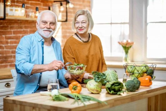 Older couple cooking a healthy meal to perserve their healthspan with nutrution.