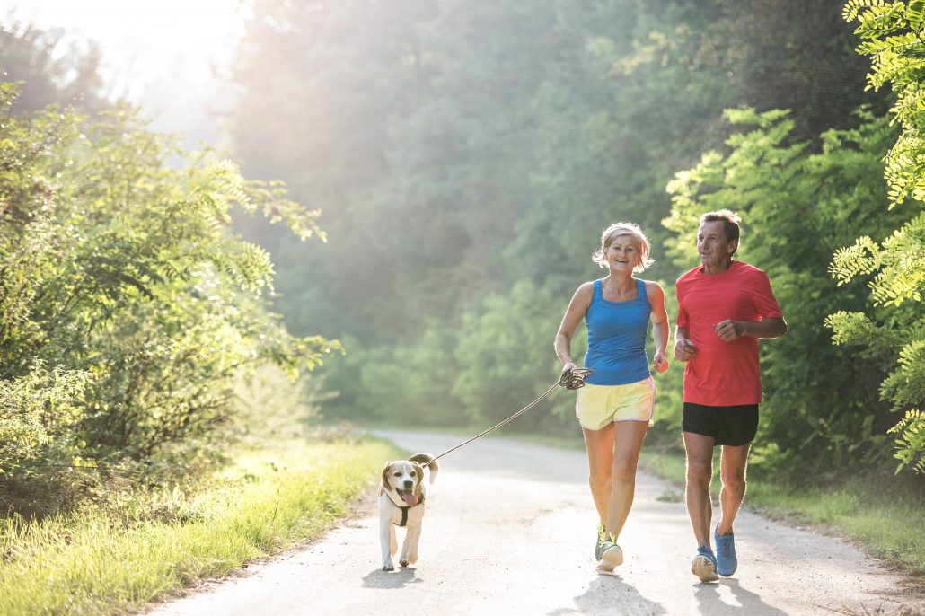 Older couple jogging with their dog
