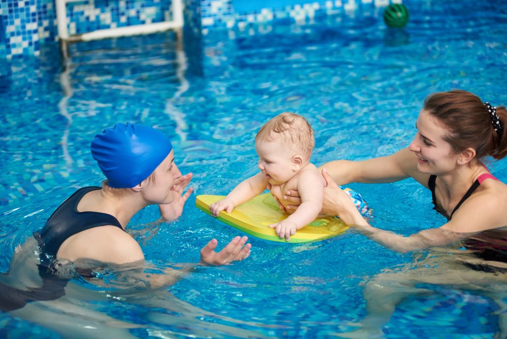 Two ladies in swimming pool with baby in the middle